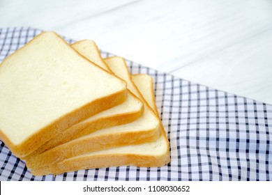 Four of sliced white bread on the table. Good for breakfast. Soft and Yummy. Eat with butter or jam or can make sandwich. Copy space.