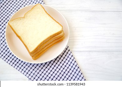 Four of sliced white bread on the table with tartan fabric. Good for breakfast. Soft and Yummy. Eat with butter, jam or can make sandwich. Copy space. Picnic.