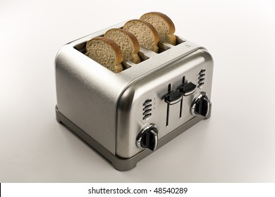Four slices of brown bread in a stainless steel toaster