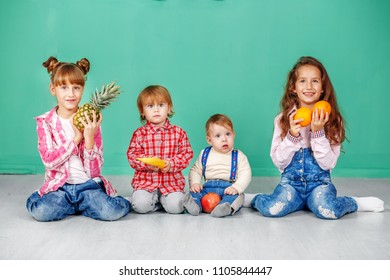 Four small children sit and hold fruit. Useful Fruits. The concept of a healthy lifestyle, food, childhood, vitamins, vegetarianism.