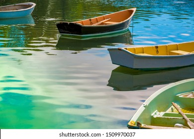 Four small colorful painted wooden rowboats with oars at anchor on a vivid blue and green ocean