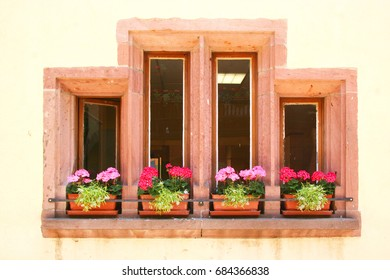four small stone window frames each with one geranium flowerpot