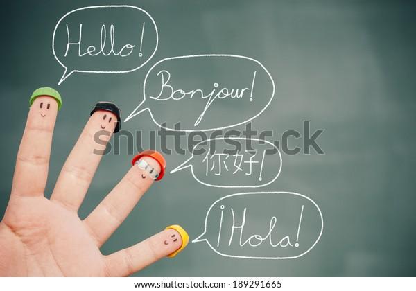 Cuatro dedos sonrientes en una pizarra diciendo adiós en inglés, francés, chino y español.