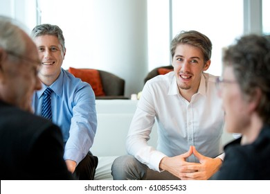 Four Smiling Business People Discussing Issues