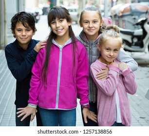 four smiling children play without parents in street on sidewalk in modern city