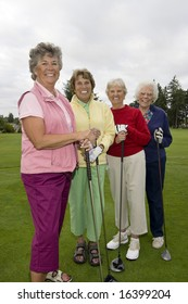 Four smiling, elderly women carrying golf clubs. Vertically framed photo.