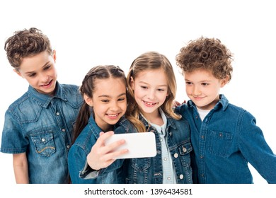 four smiling kids in denim clothes taking selfie isolated on white