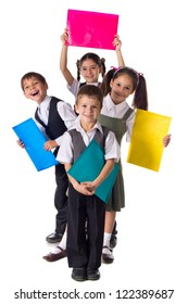 Four smiling schoolchild standing with colorful folders, isolated on white