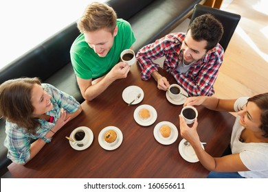 Four smiling students having a cup of coffee chatting in college canteen