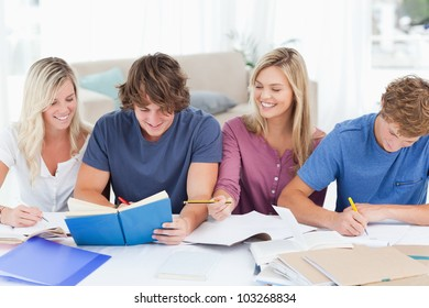 Four smiling students sitting together as they laugh while studying