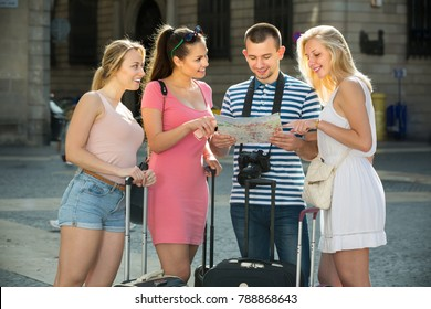 Four smiling traveling young people searching for direction using paper map in town