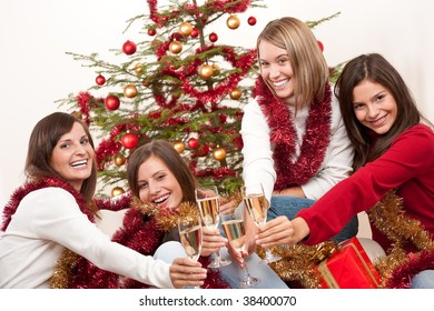 Four smiling women with glass of champagne on Christmas celebrating