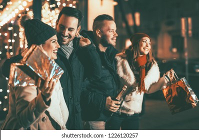 Four smiling young friends standing outside and holding many shopping paper bags and boxes in city holiday night. Selective focus. Focus on foreground.