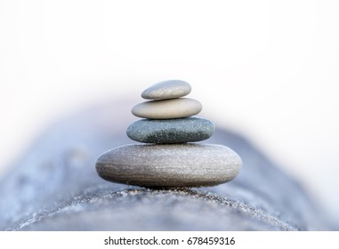 Four smooth beach stones stacked and balanced on a driftwood log, shallow depth of field, peace, balance and creation concepts