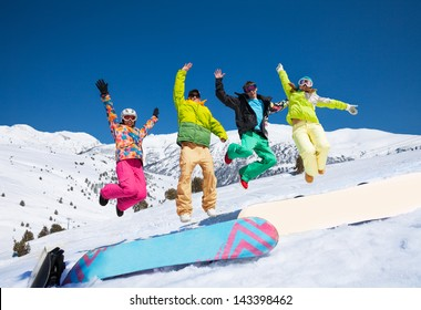 Four snowboarders friends in bright vivid clothes jumping in snow with mountains on background