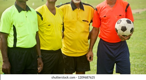 Four soccer referees standing together wearing colourful jersey unique photo