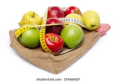 Four sorts of apple with a tape measure on a burlap bag, isolated on white