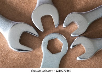 four spanner of different size lying in the direction of the hex-key brown background