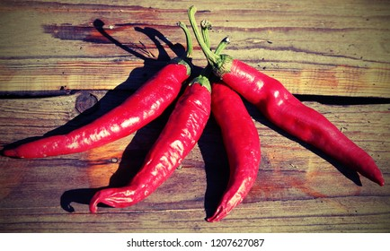 four spicy chillies on a wooden table with lomo effect