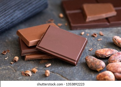 Four squares of dark and milk chocolate with small chocolate bits on grey slate next to cocoa beans. Blurred chocolate in the  background.