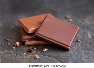 Four squares of dark and milk chocolate isolated on grey slate. Small bits of chocolate. Blur background.