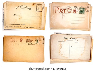 Four stacks of blank, heavily aged post cards from early 1900s.  Isolated on white.