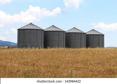 Four steel grain silo towers in rural Greece