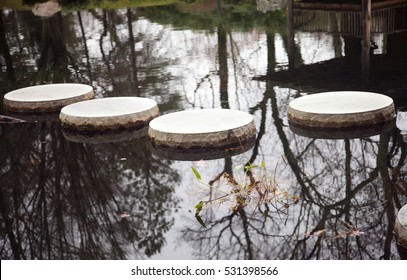 Four stepping stones in Japanese garden pond with reflection and leaves. Horizontal.