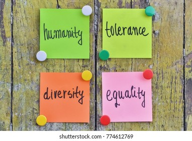 Four stickers with handwritten text about human tolerance pinned on wooden background