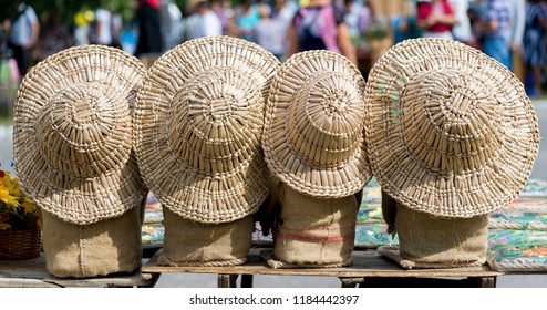 Four straw hats of different sizes on linen bags at the fair