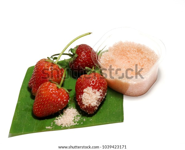 Four strawberry are on banana leaves and sugar on a white background.