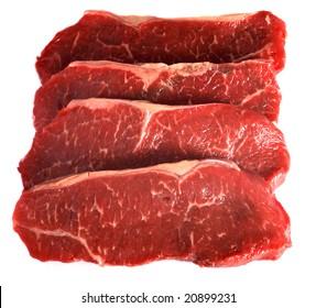 Four striploin steaks (also known as delmonico steak, Kansas City strip steak, shell steak, new york steak and porterhouse steak in various societies) on a white background