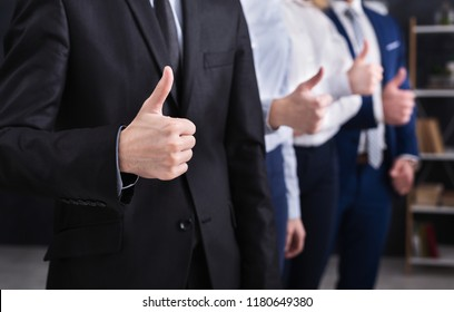 Four successful businessmen showing thumbs up standing in row in ofice