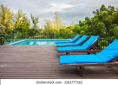 Four sun loungers on wooden decks near swimming pool. The exterior decoration on rooftop for recreation.