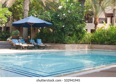 Four sun-loungers by the side of a small private pool