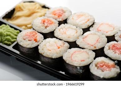 Four sushis on a black plate and white background Ebi Maki, Kani Maki Sake Maki Maguro maki.