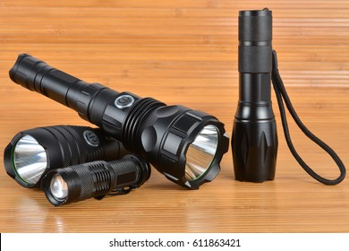 Four tactical lights on a wood background