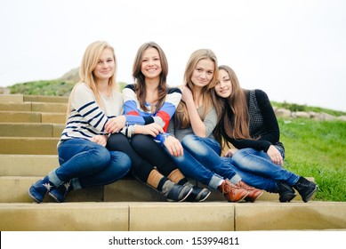 Four teen girls friends having fun happy smiling & looking at camera on the green outdoors background