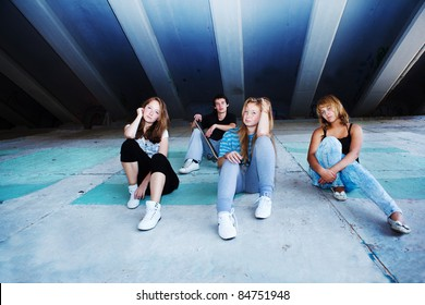 Four teenage friends sitting on concrete slabs