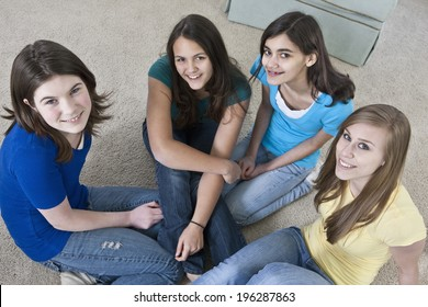 Four teenage girls relaxing in a group together on a living room carpeted floor