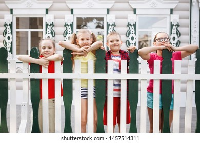 Four teenage kids are watching from behind a fence. White palisade, wooden house, happy childhood.