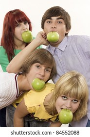 Four teenagers with green apples in mouth