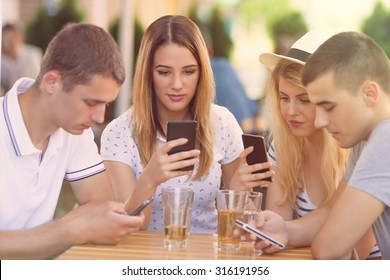 Four teenagers sitting in a cafe using their mobile phones