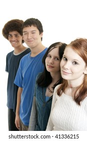 Four teens of different ethnic backgrounds smiling. Shallow DOF. Focus on front teen girl.