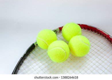 Four tennis balls on a racket