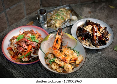Four Thai dishes: grilled king prawn with scallop and clam, beef salad with clam and vegetables, steamed fish with herbs and spices, glazed spare ribs