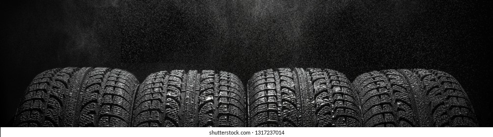 Four tires in a row with water drops over black background, copyspace for your text or advertising concept horizontal photo studio shot, nobody