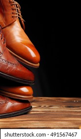 Four toes one on one of brown shoes (brogues and derby) on the wooden table.Shoes shine concept of luxury shoes