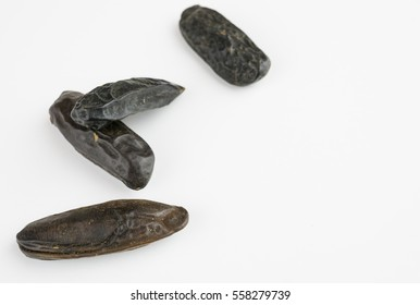 four tonka beans, isolated on white, copy space