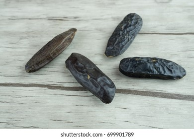 Four tonka beans on wooden background, copy space